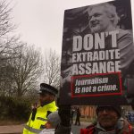 Assange supporter and police outside Belmarsh jail, London.