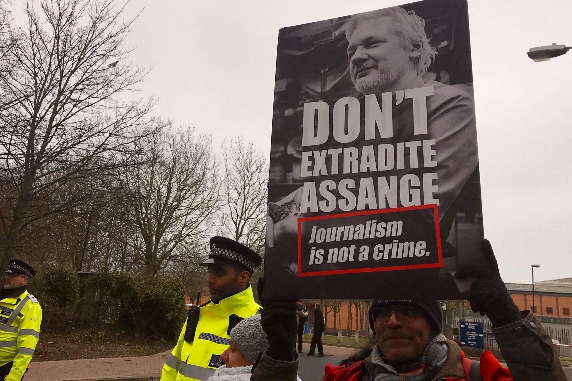 Assange supporter and police outside Belmarsh jail, London.